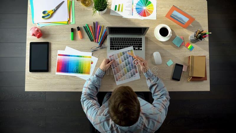 Дизайнер по интерьеру выбирая цвет на палитре и приказывая его онлайн, взгляд сверху стоковое изображение rf