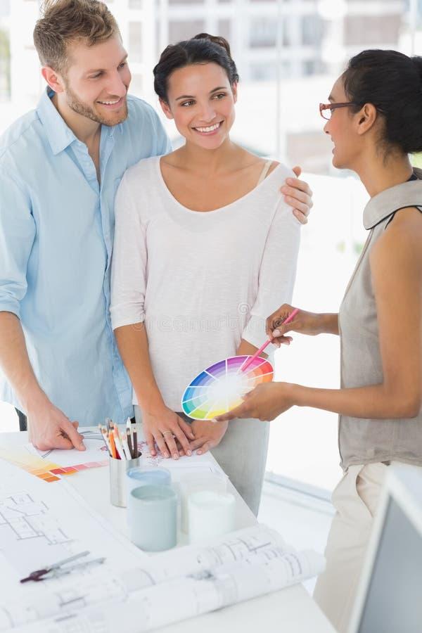 Дизайнер по интерьеру показывая колесо цвета к счастливым клиентам стоковое фото