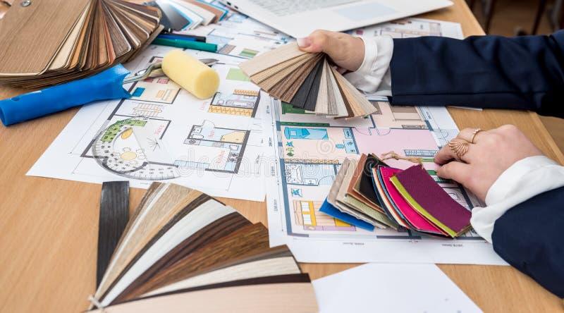 Дизайнер по интерьеру с планами образца и здания цвета на офисе стоковое фото rf