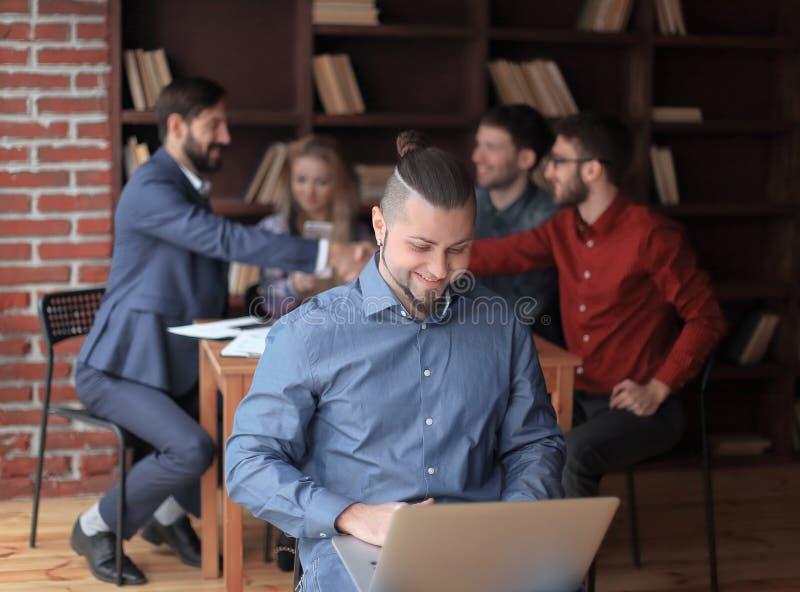 Дизайнер работая на компьтер-книжке фото на предпосылке рукопожатия деловых партнеров стоковое изображение rf