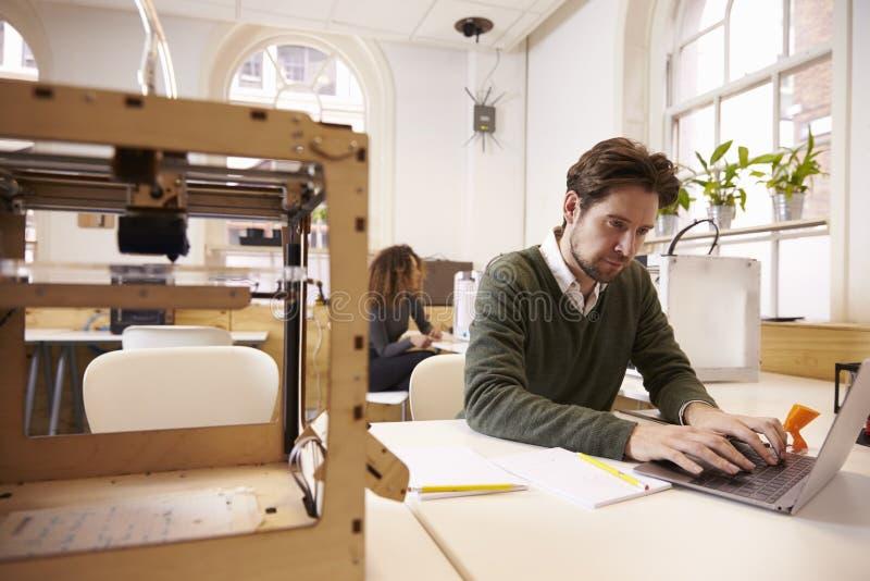 Дизайнер работая с принтером 3D и програмным обеспечением CAD в студии стоковое изображение