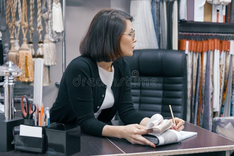 Дизайнер рабочего места женский, бизнес-леди в стеклах с ручкой тетради и образец ткани работая в офисе стоковое фото