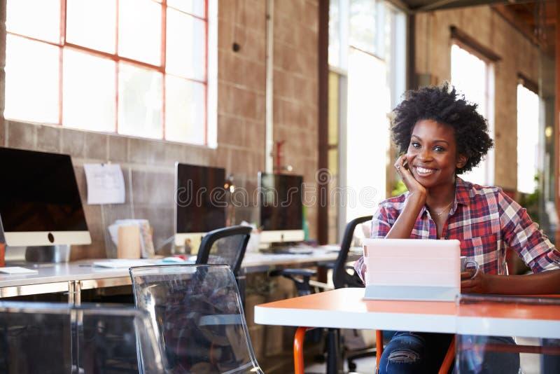 Дизайнер сидит на таблице встречи работая на таблетке цифров стоковые изображения
