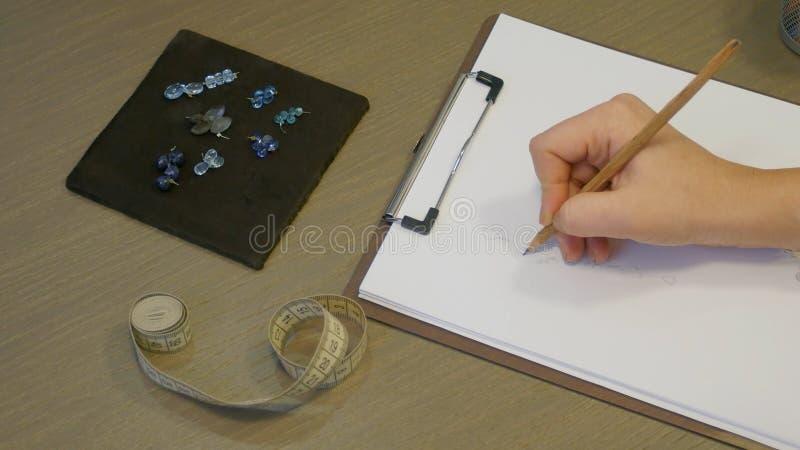 Дизайнер ювелирных изделий на работе в студии, делая эскиз к конструирует для уникально handmade серег стоковое изображение rf