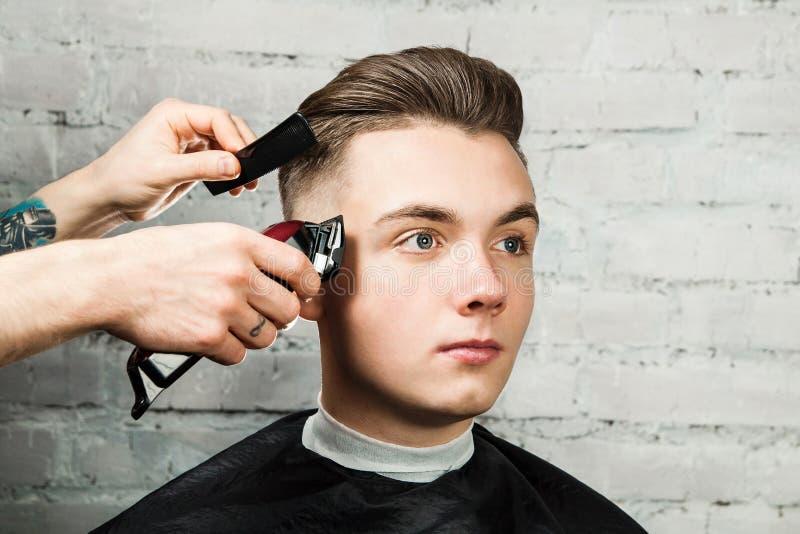 Дизайн волос парикмахера молодого парня в парикмахерскае на предпосылке кирпичной стены, парикмахере делает стиль причесок для мо стоковая фотография rf