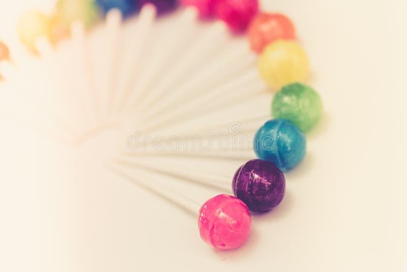 Дизайн радуги сладостных красочных леденцов на палочке стоковые изображения