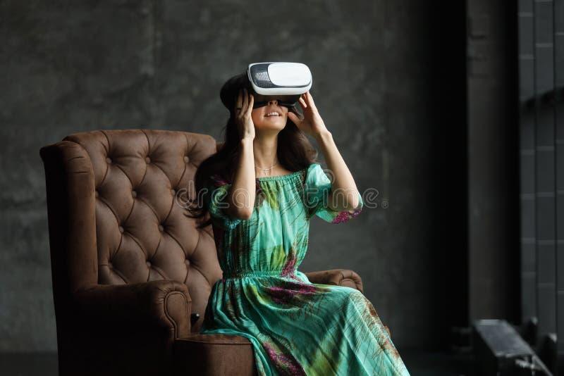 Дизайн шлемофона VR родовой и никакие логотипы, женщина с стеклами виртуальной реальности, не сидят в стуле, против темной предпо стоковое изображение rf