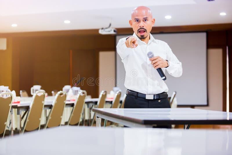 Диктор держал микрофон в его руке и показывает его forefinger к оператору на приеме с расплывчатым конференц-залом и репроектором стоковое фото rf