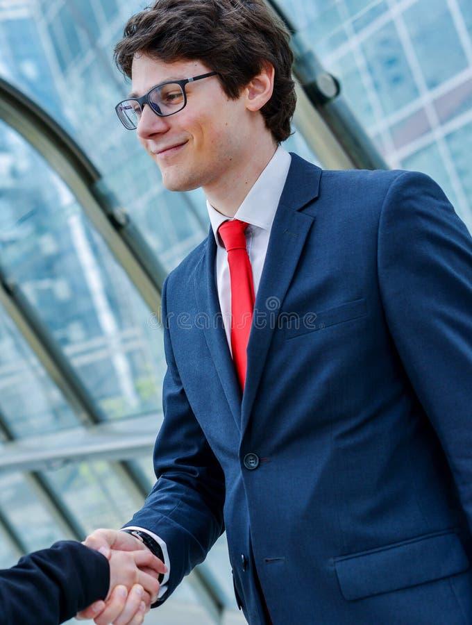 Динамика младших администраторов тряся руки стоковое фото rf