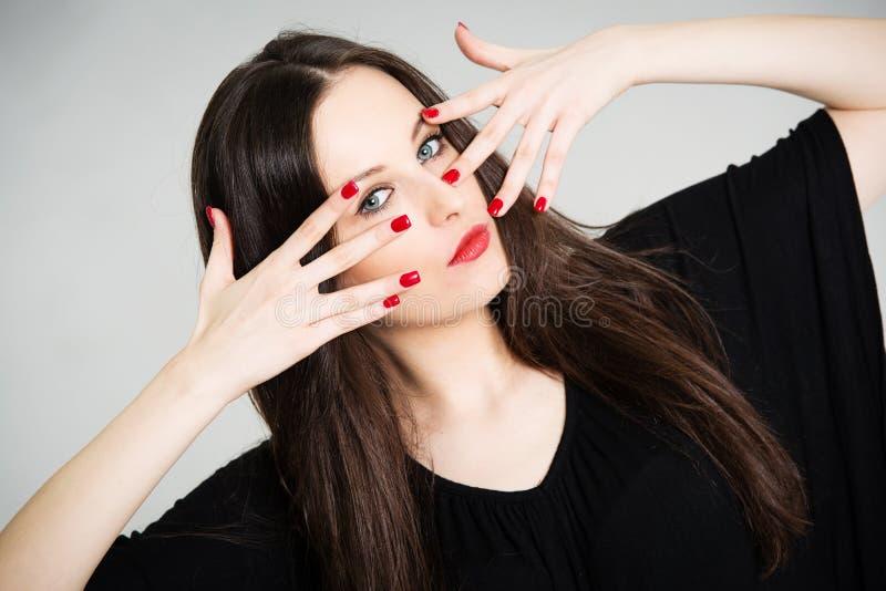 Портрет красивейшего брюнет с красными ногтями стоковые изображения rf