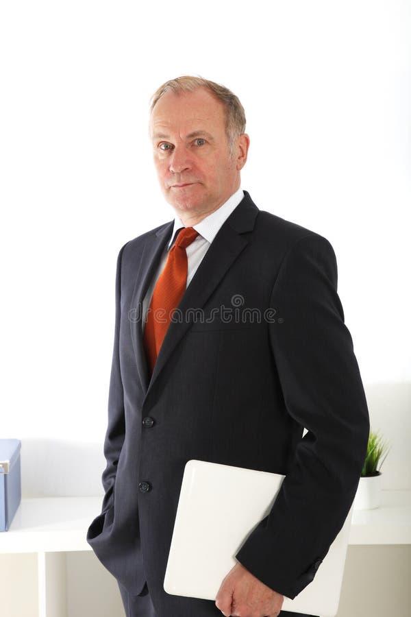 Директор компании стоя с компьтер-книжкой стоковое фото