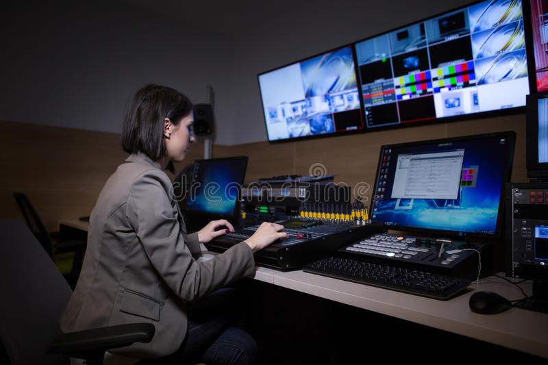 Директор ТВ на редакторе в студии Директор ТВ говоря к телевизионному микшеру в галерее передачи телевидения Женщина сидеть на mi стоковые изображения rf
