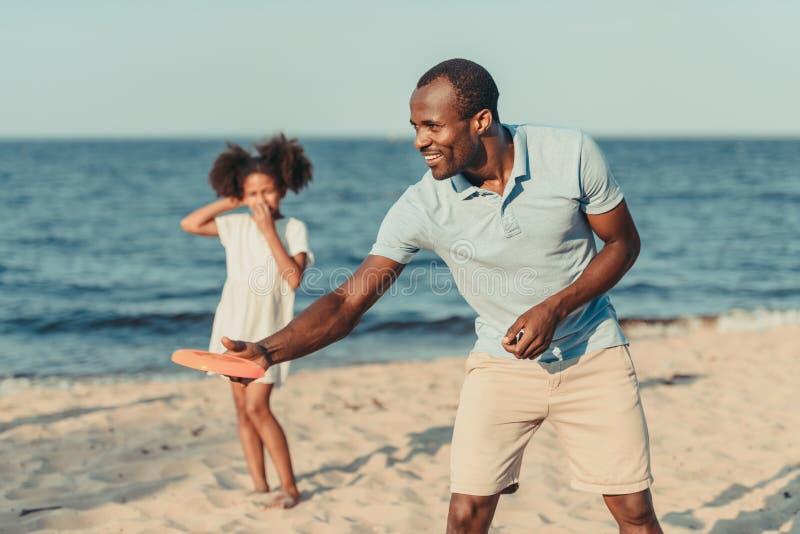 диск летания счастливого Афро-американского отца бросая пока играющ с маленькой дочерью стоковые изображения