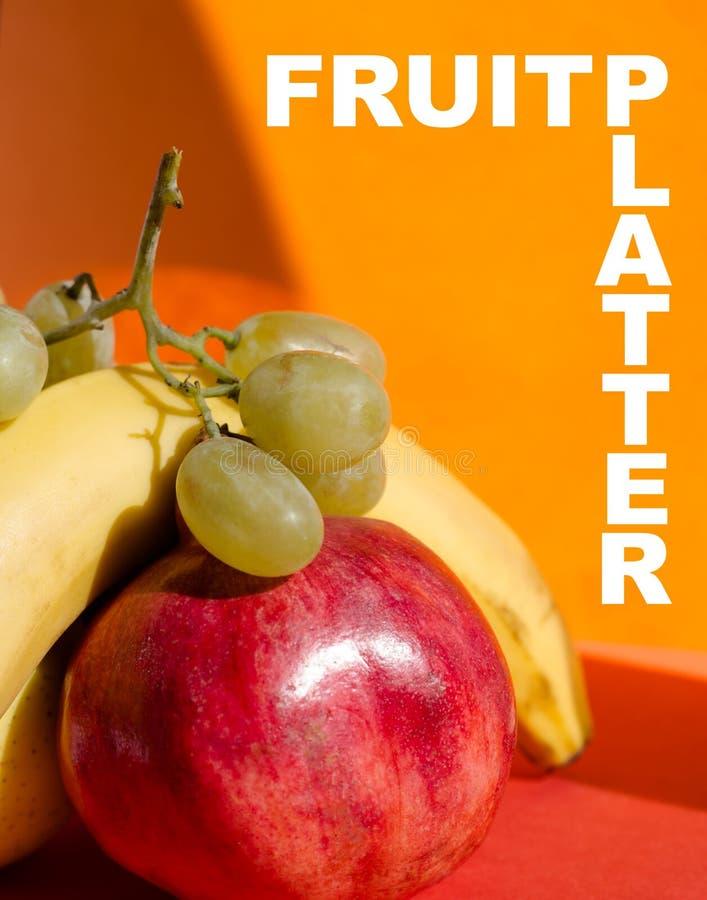 ДИСК ПЛОДООВОЩ: золотые яблоко, банан, гранатовое дерево и виноградины стоковые фото