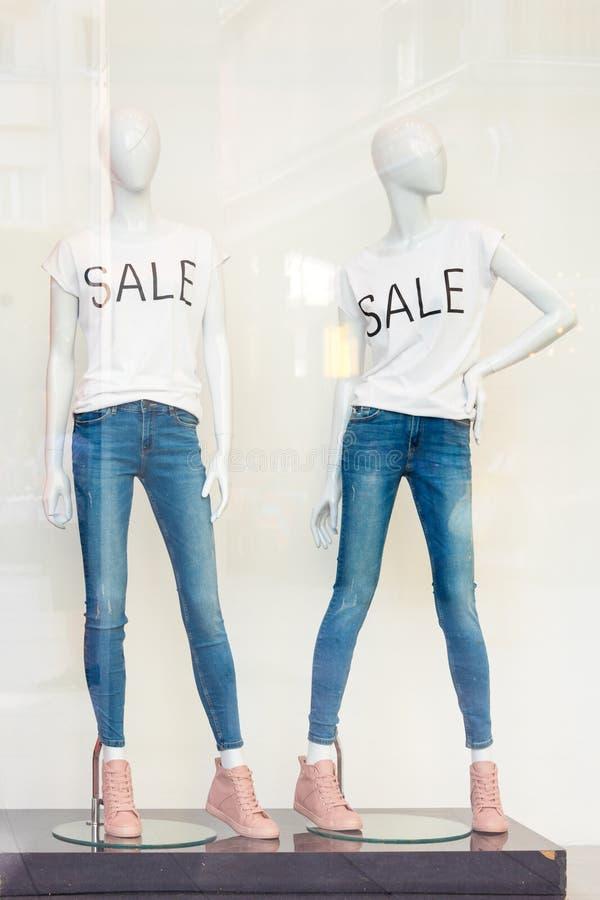 Дисплей окна продажи покупок при манекены нося футболки с продажей текста Куклы в магазине Продажа и мода стоковая фотография