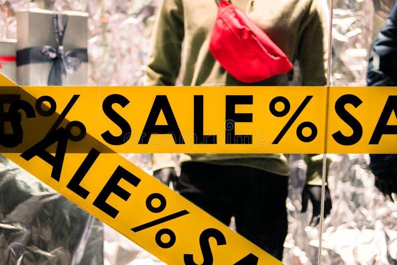 Дисплей окна с ПРОДАЖЕЙ текста в магазине Предложение скидки на магазине одежды стоковая фотография rf
