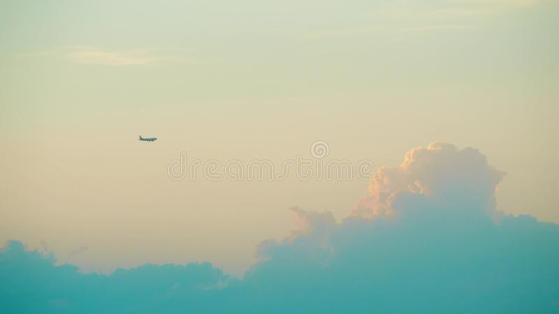 Дистантное коммерчески летание самолета против красивого захода солнца заволакивает стоковое фото