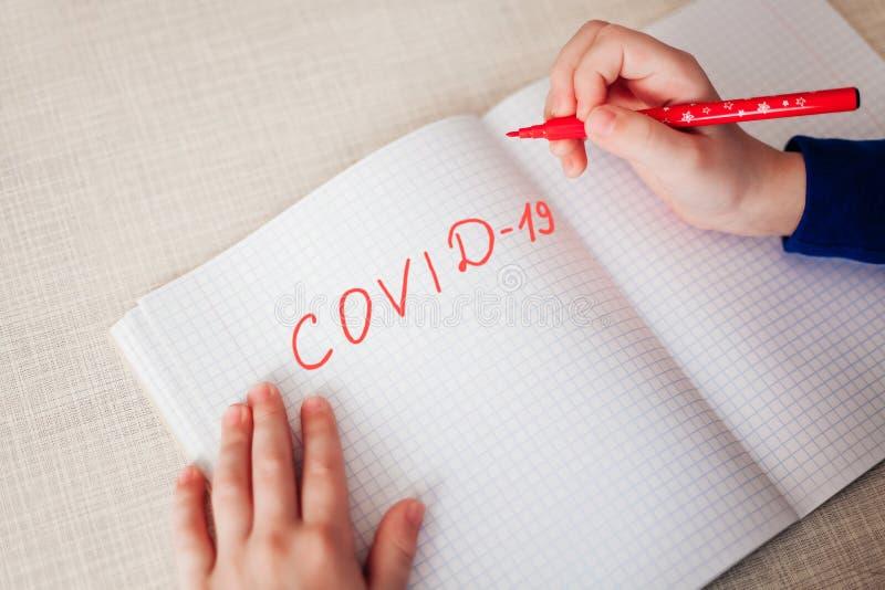 Дистанционное обучение онлайн образование Надпись 'Covid 19' с красной ручкой в записной книжке, которая лежит на деревянном стол стоковое фото