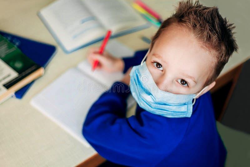 Дистанционное обучение онлайн образование Школьник в защитной маске сидит за столом и пишет в записной книжке На столе стоковая фотография