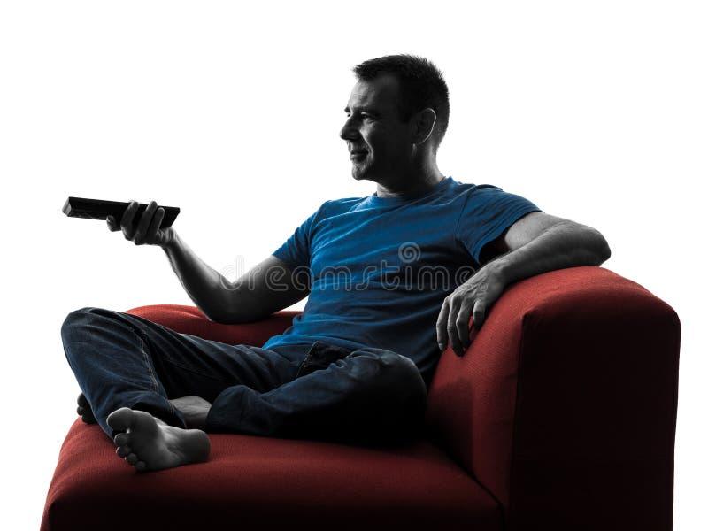 Дистанционное управление тренера софы человека смотря ТВ стоковое фото rf