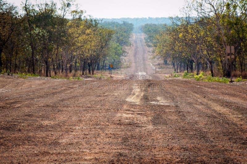 Длинная прямая красная грязная улица в регионе захолустья Кимберли Австралии стоковые изображения
