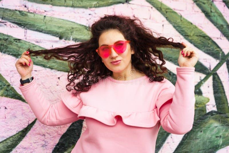 Длинная с волосами курчавая женщина брюнета в розовом платье и розовы стоковые фото