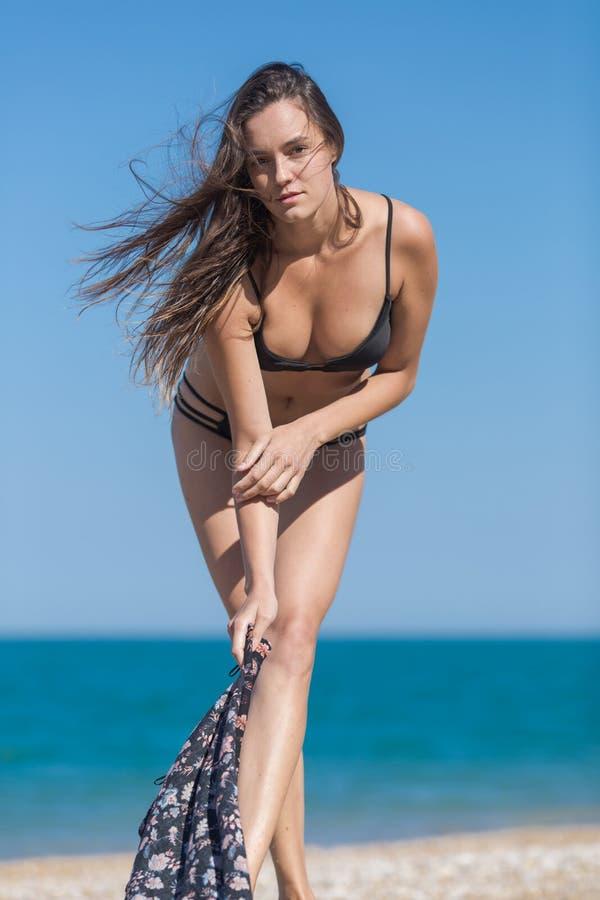 Длинная с волосами молодая женщина в черном бикини против моря стоковая фотография