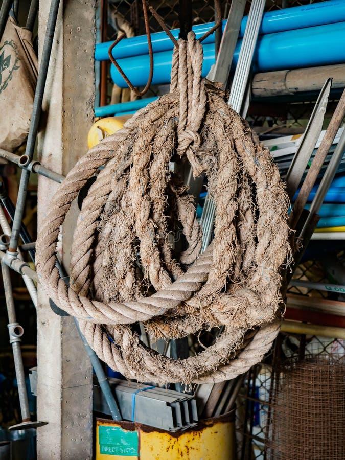Длинная толстая спиральная веревочка с некоторым домом, висит с крюком стоковые фото