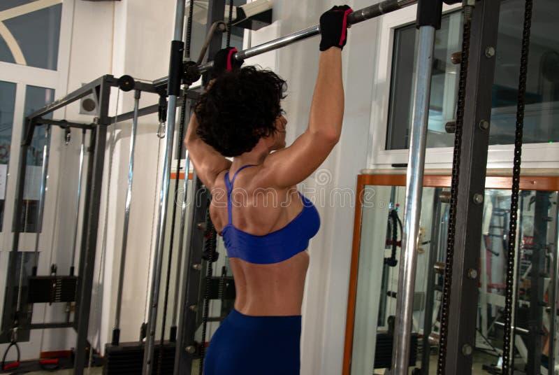 длинной с Полу портрет молодой мышечной девушки с голубым лифом, она использует multipower в спортзале стоковое изображение