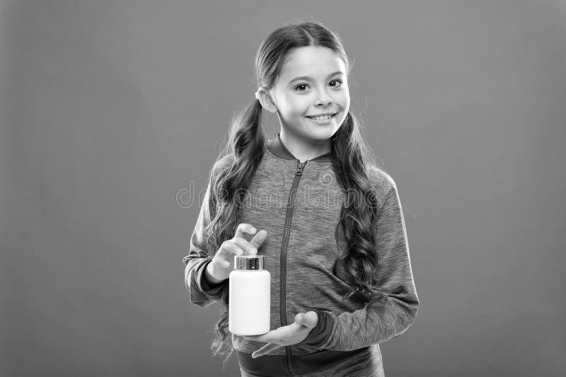 Длинные волосы держат бутылку с лекарствами Концепция витамина Потребность в витаминных добавках Девочки-милые дети принимают лек стоковые фотографии rf