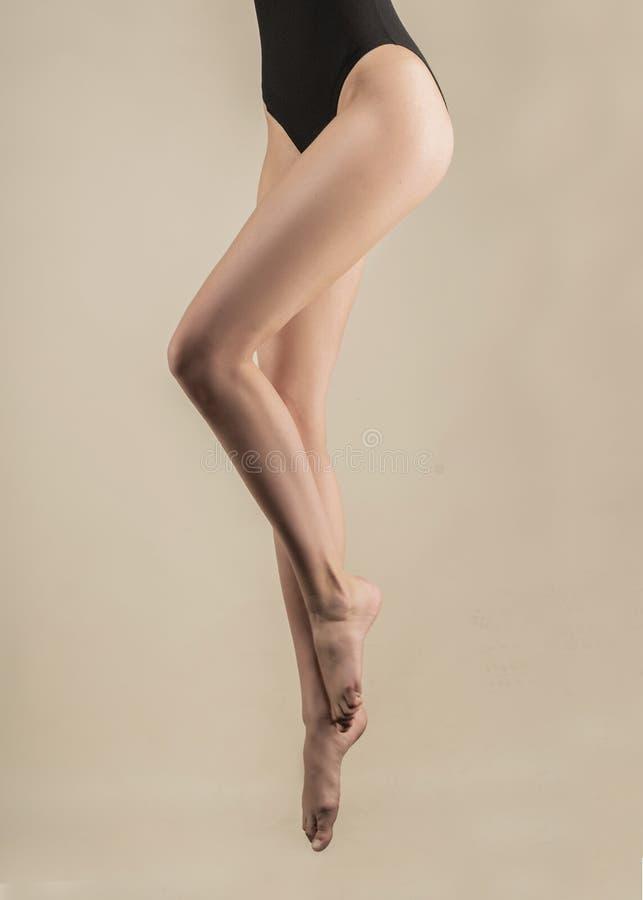 Длинные красивые худенькие женские ноги вися в воздухе в скачке Девушка одета в черном теле Изолированный на свете стоковые фото