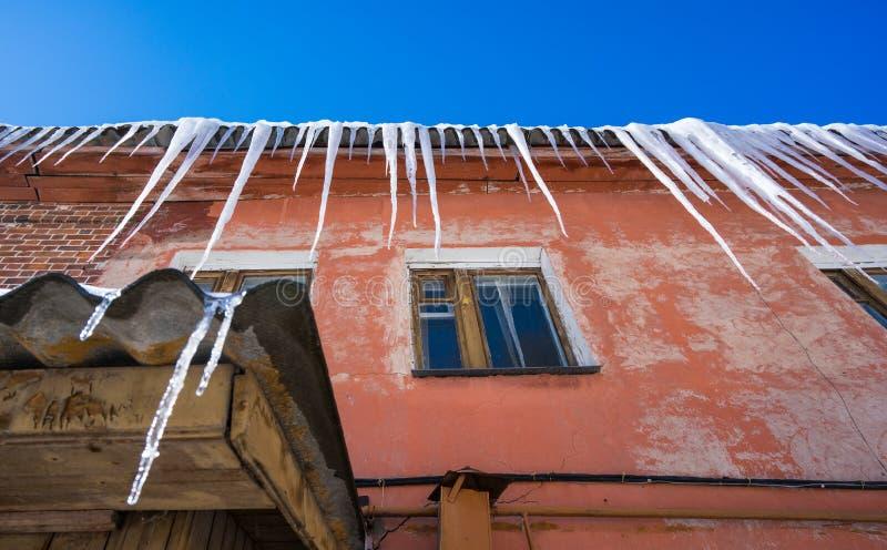 Длинные сосульки висят на старом доме на солнечный день r Перемещение к России стоковое фото rf