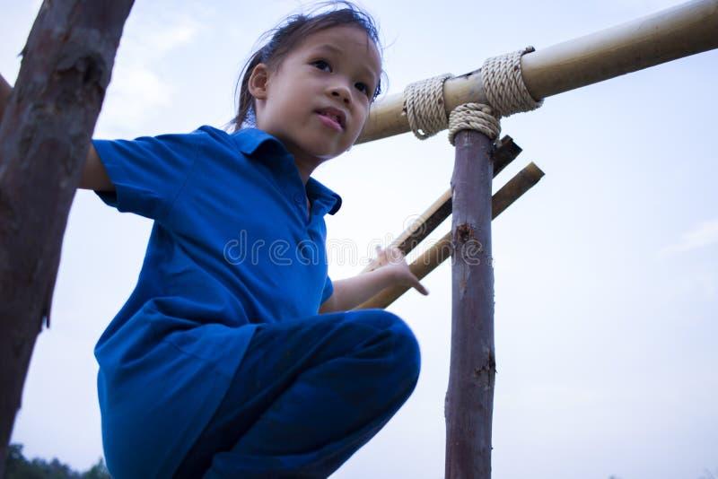 Длинный бег мальчика волос и взбираться на лестнице в дороге поля риса стоковое изображение rf