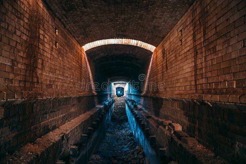 Длинный подземный тоннель кирпича или промышленная атмосфера коридора, страшного и ужаса, перспектива стоковые фото