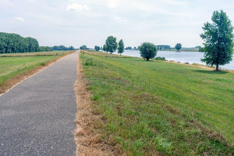 Длинный путь велосипеда вдоль широкого голландского реки стоковое изображение rf