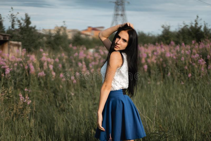 Длинн-с волосами девушка в зеленом поле с цветками стоковое фото rf