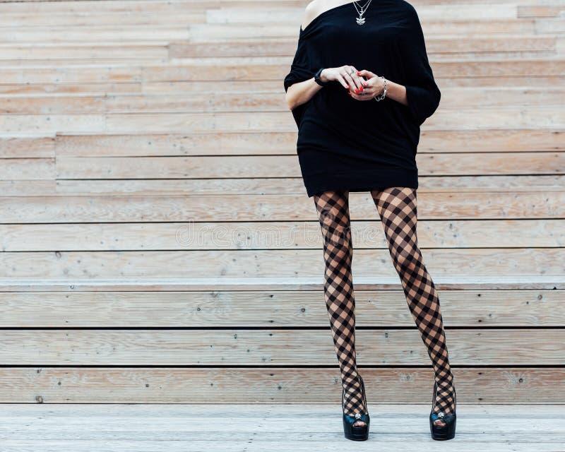 Длинн-шагающая девушка в модном колготки, черном платье и черноте высоко-накренила ботинки представляя в лете на деревянных шагах стоковое изображение rf