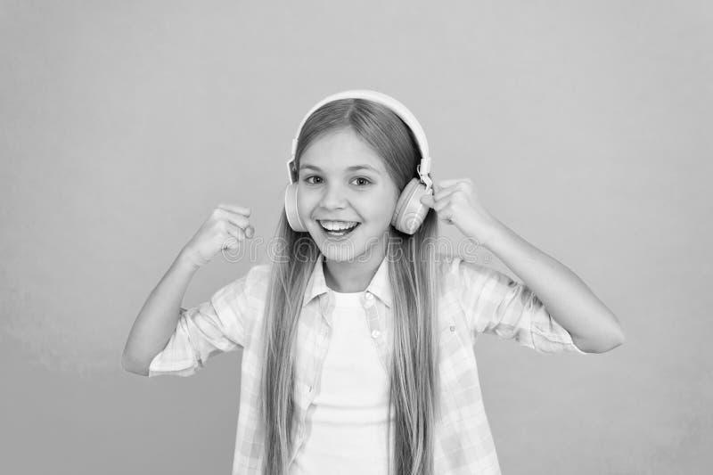 Для приятной музыкальной выдержки Ребенок маленькой девочки слушая музыку Счастливый маленький ребенок наслаждается музыкой играя стоковое фото