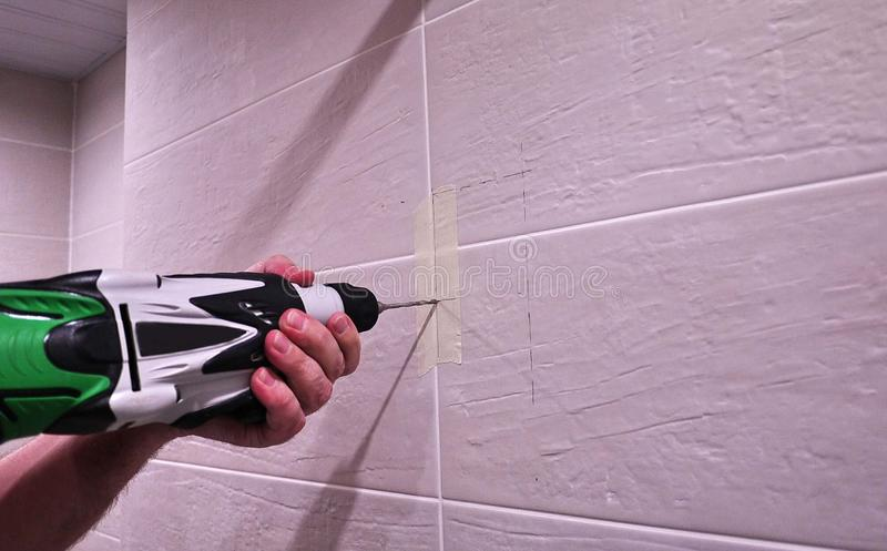 Человек работая со сверлом Для ремонтов и других рутинных работ по дому r стоковая фотография