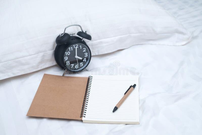 Дневник или тетрадь и будильник года сбора винограда на кровати в спальне на h стоковая фотография