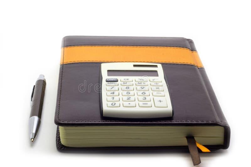 Дневник с калькулятором и ручка на белой предпосылке, комплекте коммерческого директора стоковая фотография rf