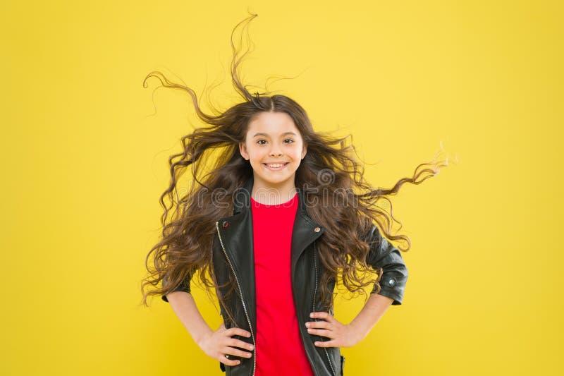 Добавление заботы к ее волосам Усмехаться прелестного небольшого ребенка девушки счастливый с длинными волнистыми волосами брюнет стоковая фотография