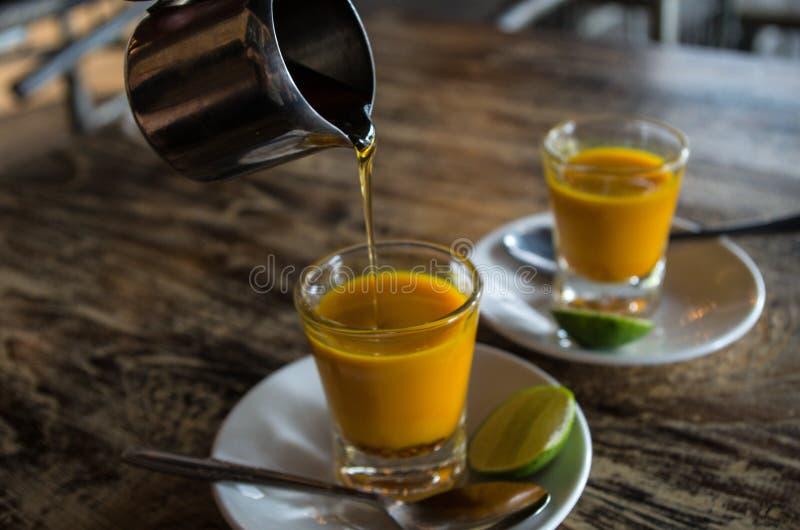 Добавлять мед до 2 здоровых съемки jamu в конце-вверх без руки стоковое изображение rf