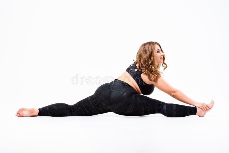 Добавочная модель размера в sportswear, жирной женщине делая разминку на белой предпосылке, концепции тела положительной стоковые изображения rf