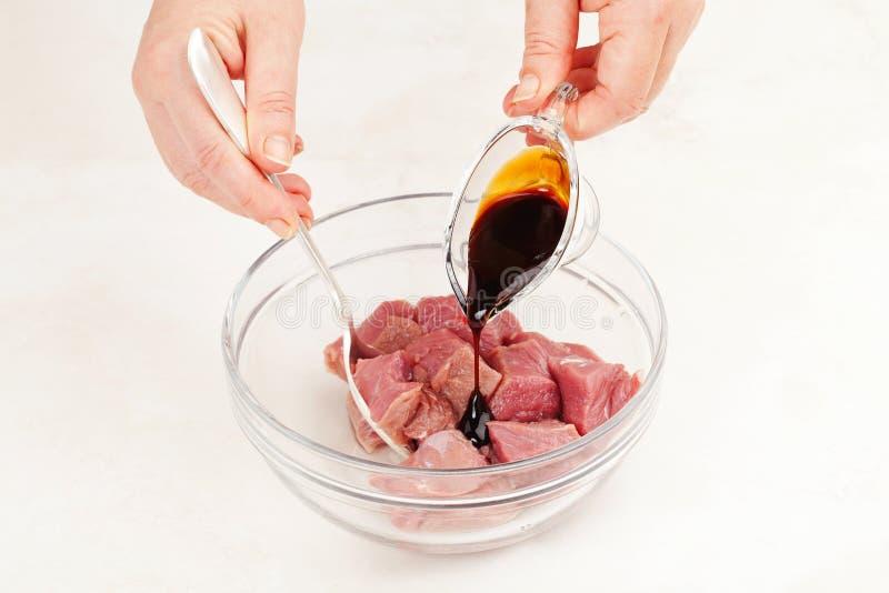 Добавьте соус к мясу стоковые фото