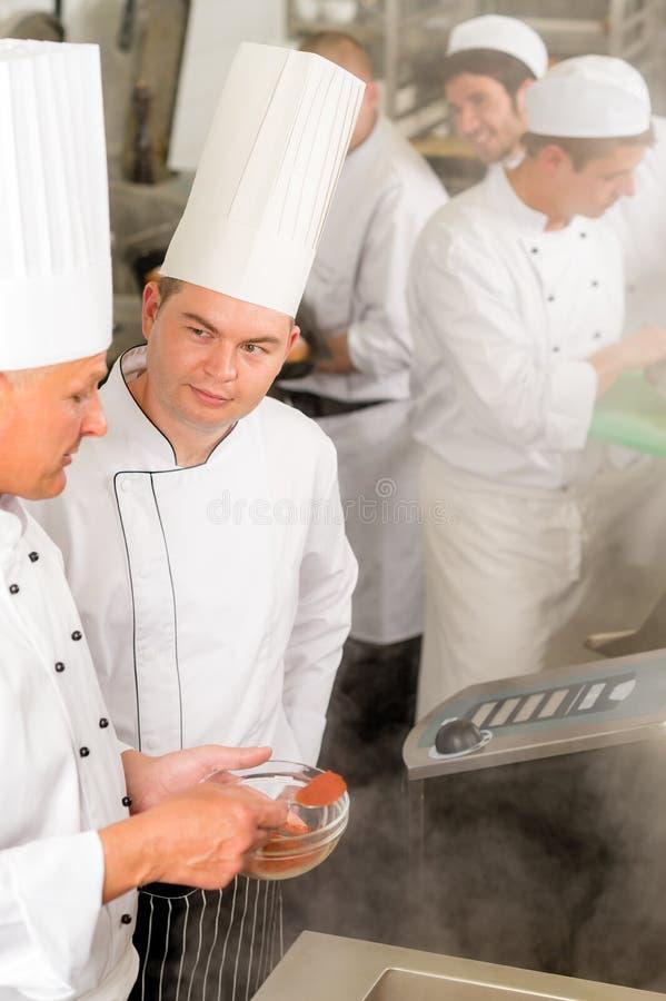 добавьте специю профессионала кухни еды кашевара шеф-повара стоковые фото