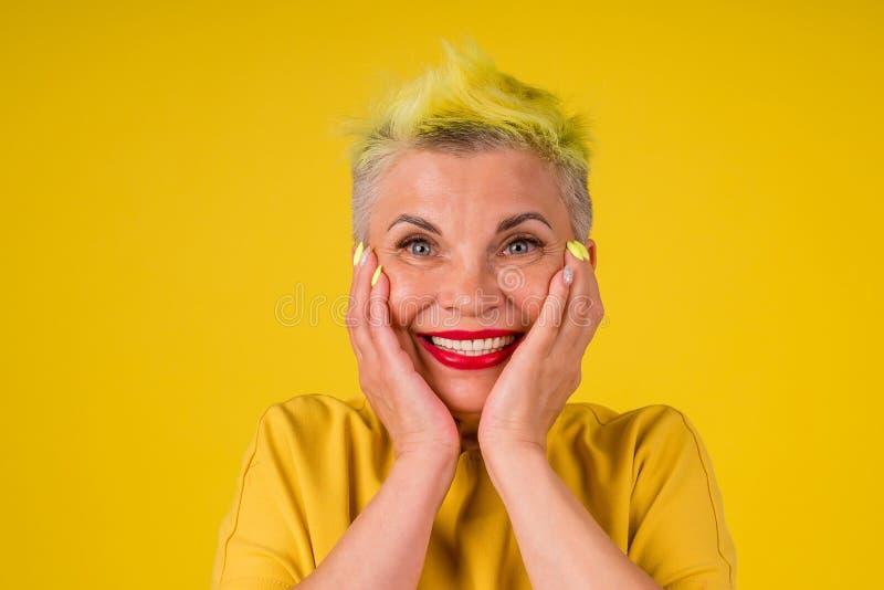 Добрая позитивная зрелая женщина с цветными, желтыми, окрашенными волосами, красная  помада на губах изумлена, глядя на снег Стоковое Изображение - изображение  насчитывающей снег, зрелая: 162119573