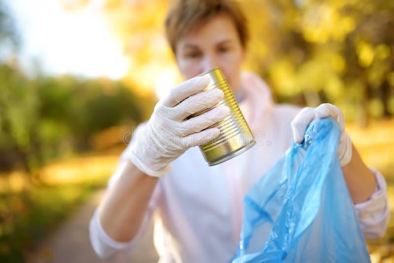 Добровольная рудоразборка вверх по отбросу и установка его в biodegradable мешок для мусора на outdoors стоковые изображения rf
