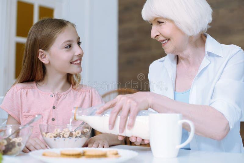 Добросердечная девушка смотря мягко на ее бабушке стоковое фото rf