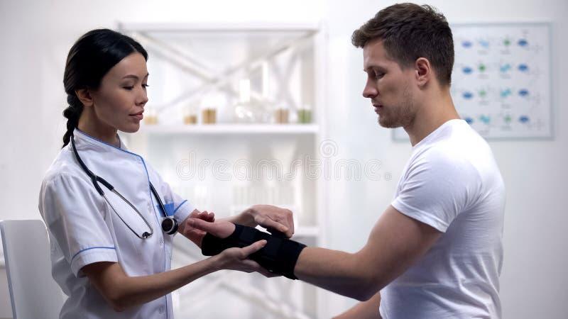 Добросердечный врач прикладывая пациента расчалки запястья титана усмехаясь мужского, реабилитации стоковое изображение rf